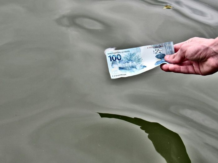 Cropped Hand Holding Paper Currency By Lake