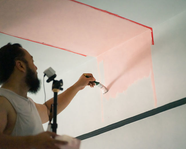 Man holding camera while painting on wall