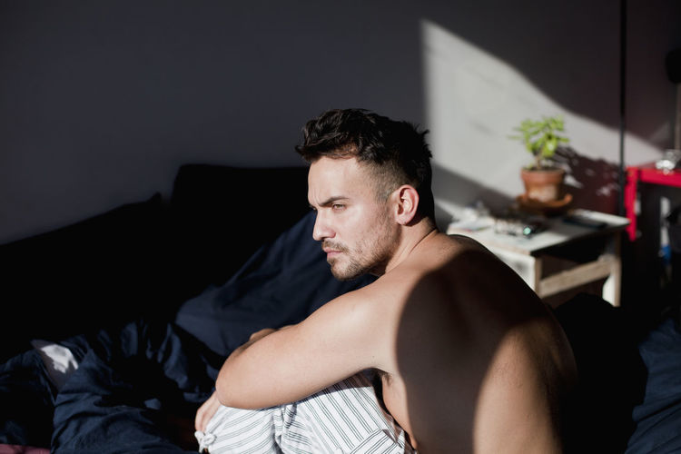 Young man looking away while sitting on sofa at home