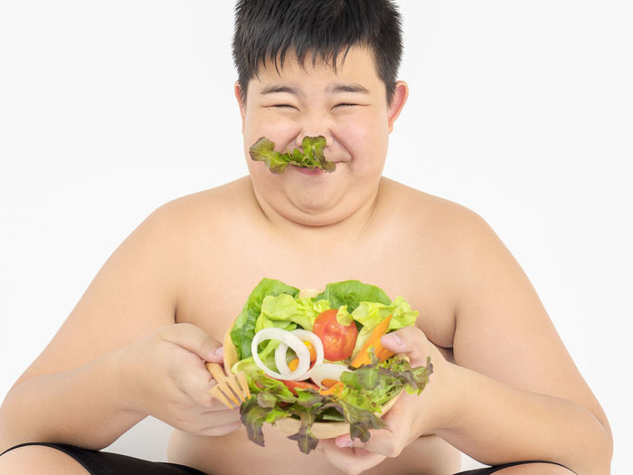 Close-up of boy holding bowl of salad making face against white background
