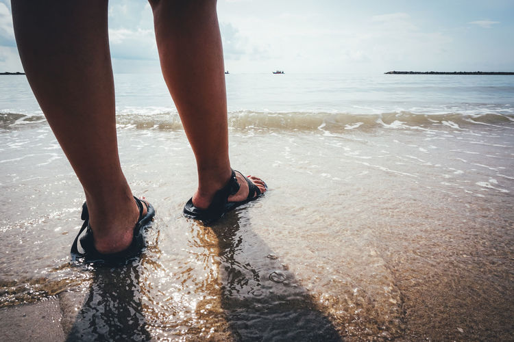 Summer Vacation and Travel Concept. Close Up of Female Legs Stand on Beach Sea Water Beach Human Leg Land Low Section Body Part Human Body Part Real People One Person Nature Sand Day Sky barefoot Leisure Activity Horizon Horizon Over Water Outdoors Human Foot