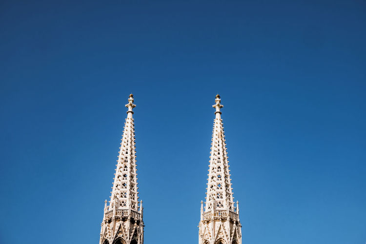 Low angle view of church towers against blue sky in vienna