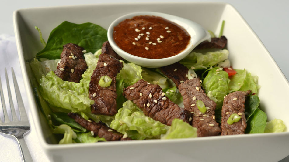 Grilled Steak Salad: with Asian style dressing on the side and garnished with sesame seeds. Close-up from above. Appetiser Appetizer Asian Beef Salad Asian Dressing Asian Food Bowl Close Up Close-up Cucumber First Course Food Food And Drink Grilled Steak Strips Healthy Eating Keto Ketogenic Diet Salad Lunch Red Pepper Romaine Lettuce Salad Salad Dressing Sesame Seeds Steak Steak Salad White