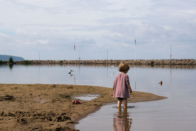 Rear View Of Girl Standing In Lake Against Cloudy Sky