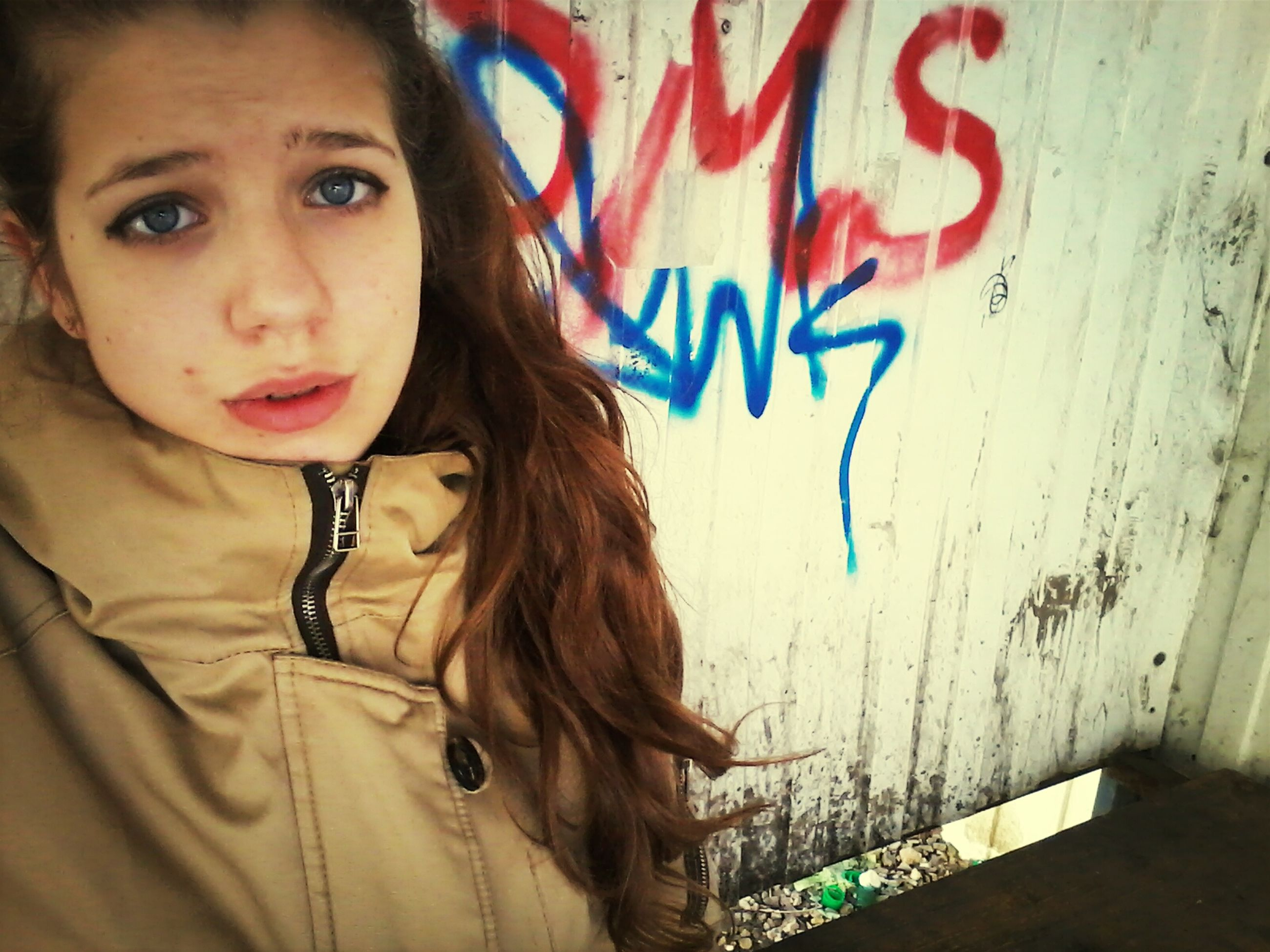 person, lifestyles, text, young adult, wall - building feature, graffiti, front view, leisure activity, young women, looking at camera, portrait, western script, communication, long hair, casual clothing, standing, waist up, headshot