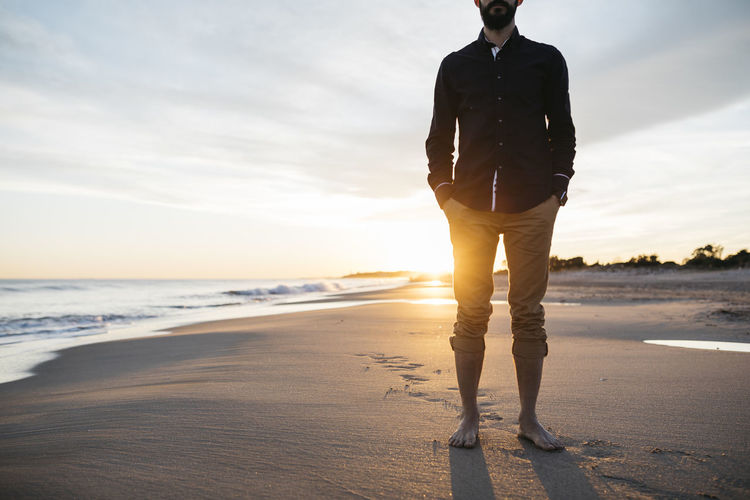 Low Section Of Mid Adult Man Standing At Beach Against Sky During Sunset