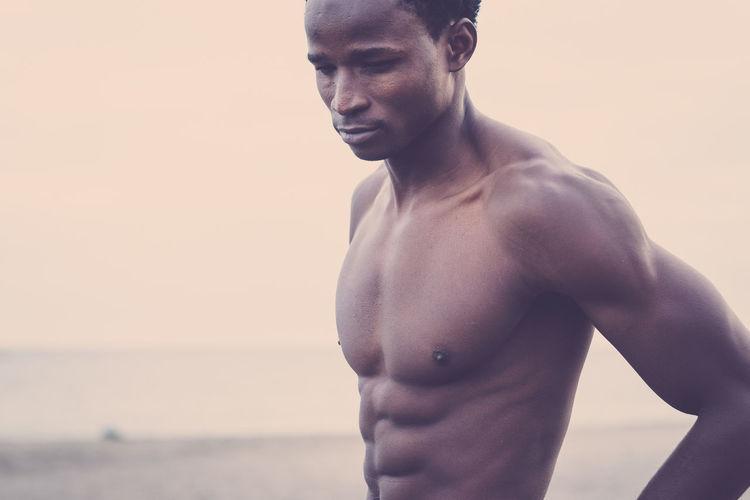 Shirtless muscular man standing at beach