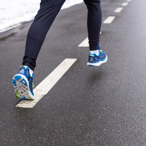 Legs of running man in sports shoes and pants. Runner on the road track. Human Leg Low Section Road Human Body Part Body Part Real People Lifestyles One Person City Day Transportation Shoe Balance Motion Running Sport Street Leisure Activity Healthy Lifestyle Human Foot Outdoors Skill  Human Limb Running Runner