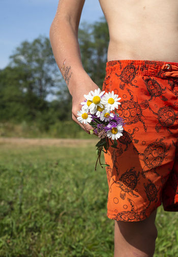 A small bouquet of wildflowers in the hands of a boy. temporary tattoo on a child's hand.