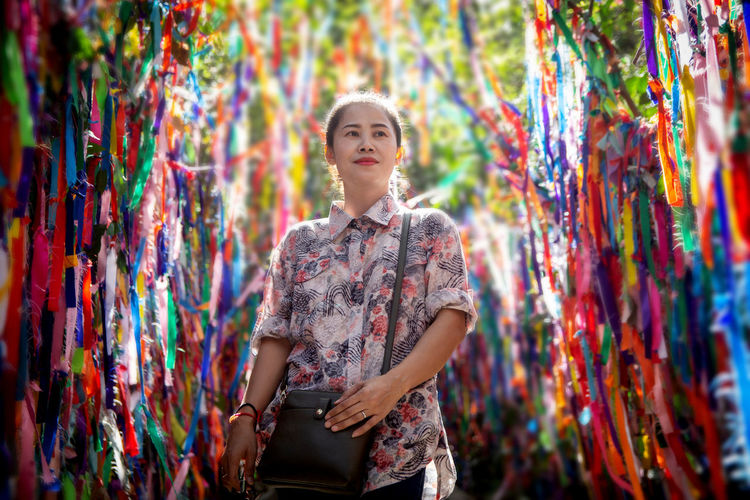 Woman standing amidst colorful prayer ribbons