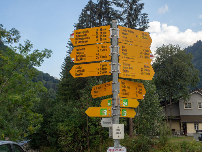Low angle view of yellow sign by trees against sky