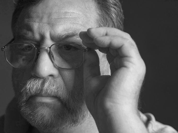 Close-Up Of Thoughtful Man With Eyeglasses Against Black Background