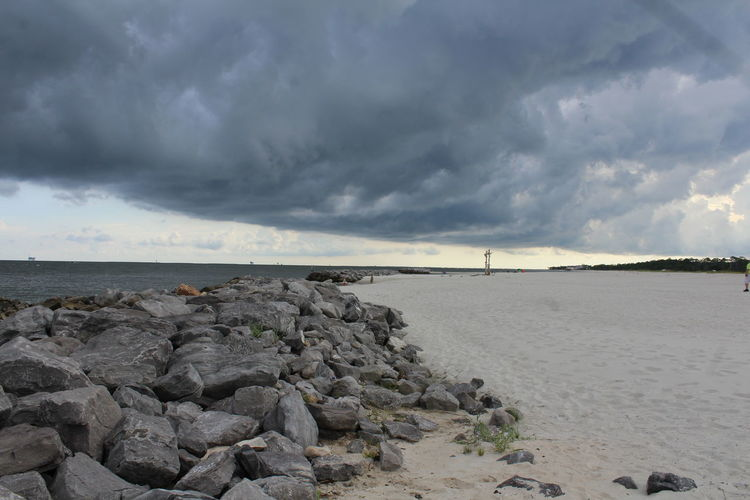 Scenic view of beach and sea against storm clouds