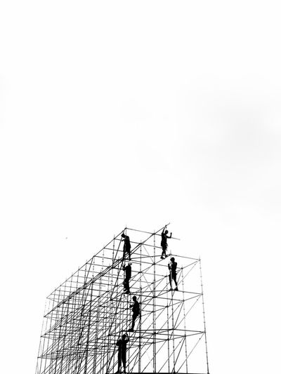 Low angle view of silhouette crane at construction site against sky