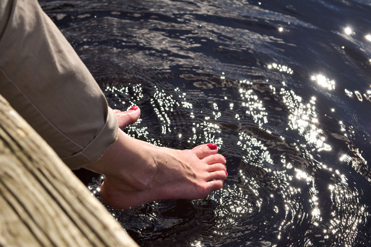 High angle view of person hand in sea