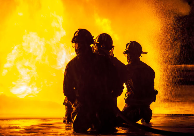 Rear view of silhouette firefighters crouching against fire at night