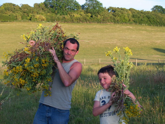 Portrait Of Father With Son Carrying Flowers On Shoulders While Standing At Farm