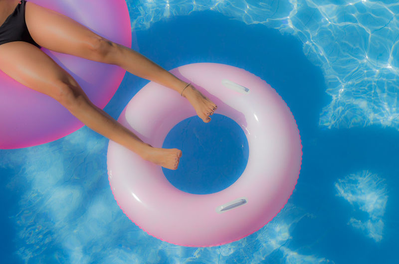 Lows section of woman relaxing on inflatable ring in swimming pool