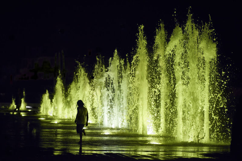 play Green Colors Fountain Child Childhood Full Length Illuminated Motion Night One Person One Young Woman Only Outdoors People Play Real People Rear View Silhouette Standing Water Young Adult