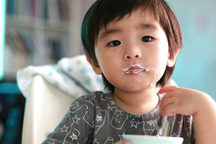 Close-up portrait of messy boy having food at home