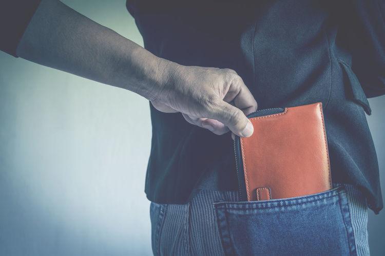 Cropped hand burglar removing wallet from man pocket