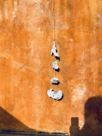 Close-up of key hanging on rock against wall