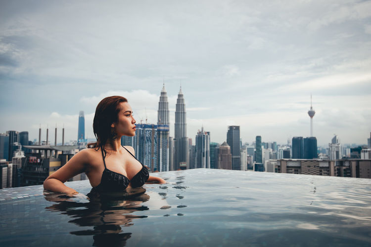Young woman in swimming pool against buildings in city