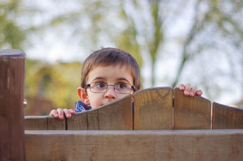 Cute Boy Looking Away While Standing By Closed Wooden Entrance Gate