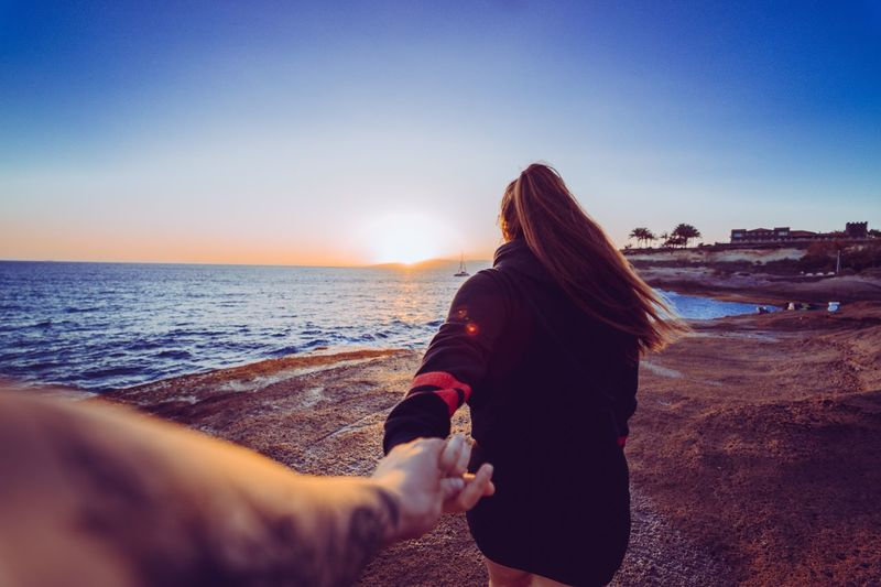 Cropped Image Of Man Holding Woman Hand At Beach During Sunset