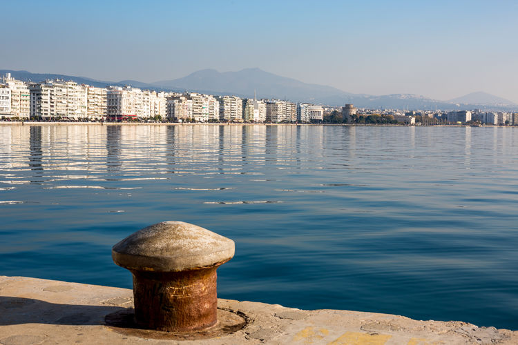 Embankment of Thessaloniki, Greece with reflections in the sea water in a clear sky afternoon Thessaloniki Architecture Beauty In Nature Building Exterior Built Structure City Clear Sky Day Greece Mountain Mountain Range Nature No People Outdoors Post Reflection Sea Sky Sunlight Tranquility Water