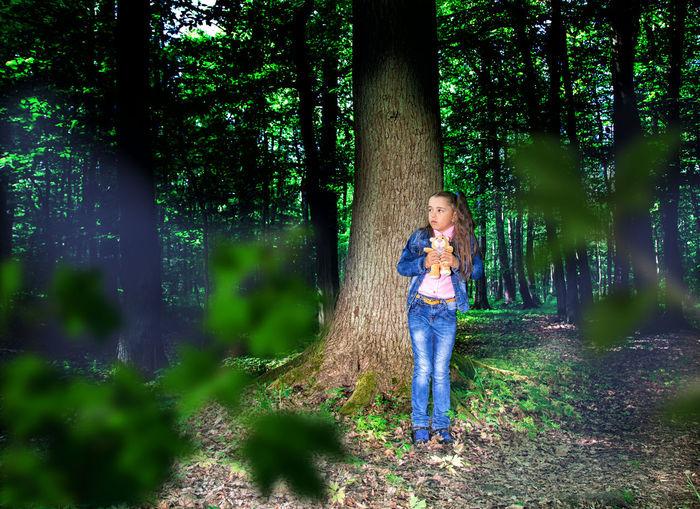 Full length of girl standing against tree trunk in forest