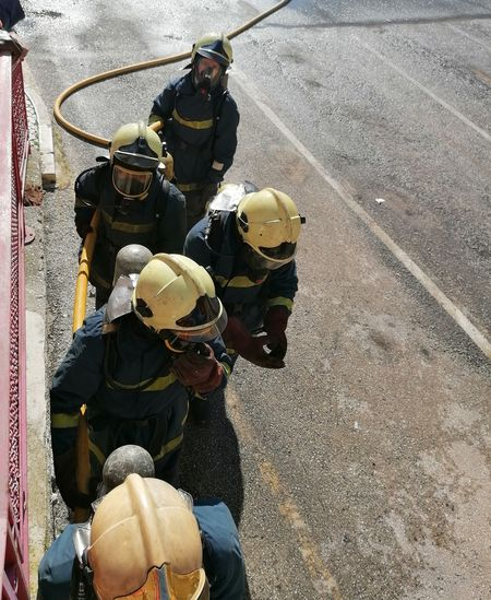 High angle view of firefighters standing on road