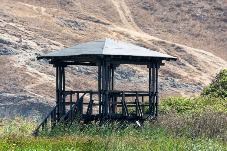 Built structure on field against mountain