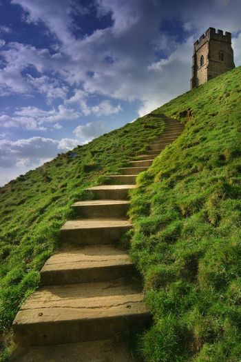 Glastonbury GlastonburyTor Leading Lines Steps Tor Architecture Building Exterior Built Structure Cloud - Sky Day Direction Glastonbury Tor Grass Green Color Hill History Lead The Way Nature No People Outdoors Sky Staircase The Past The Way Forward Wall The Architect - 2018 EyeEm Awards The Great Outdoors - 2018 EyeEm Awards The Traveler - 2018 EyeEm Awards Summer Road Tripping