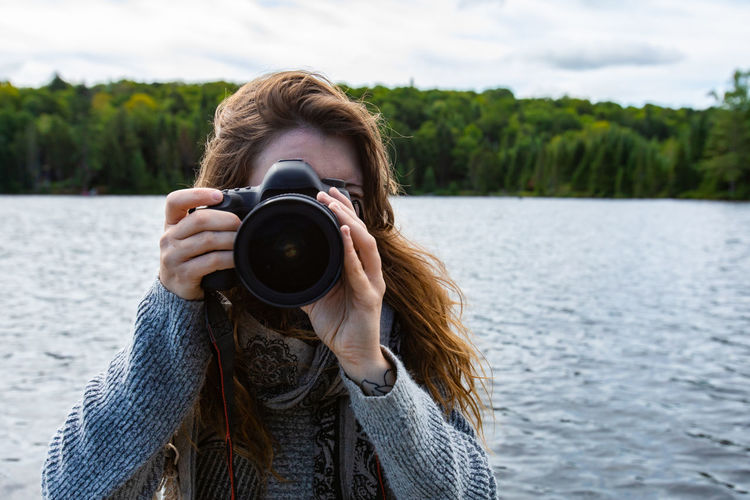 Portrait of woman photographing by lake