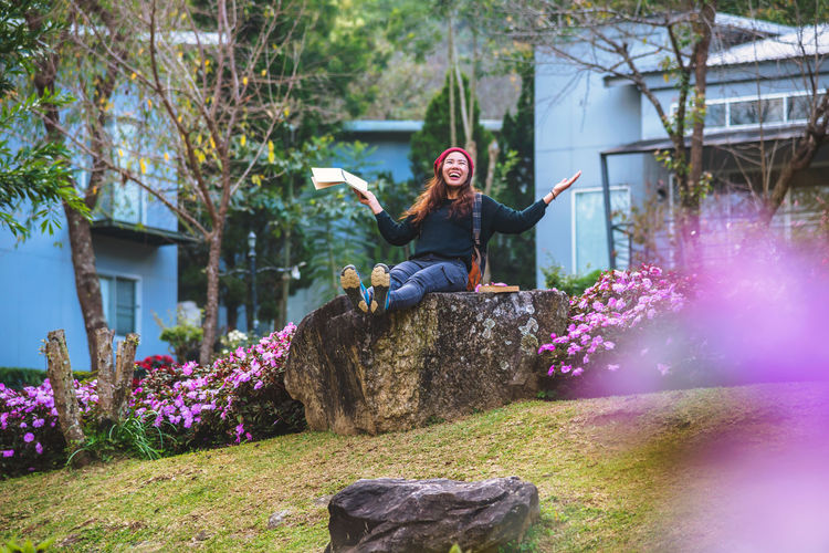 Smiling woman sitting on rock at park