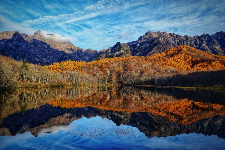 Scenic view of lake by mountains during autumn