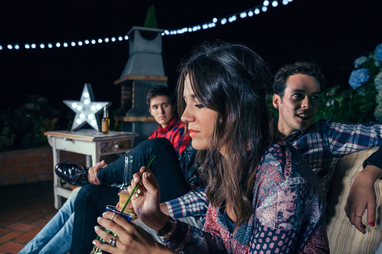 Portrait of thoughtful young woman holding cocktail with her friends in a outdoors party. Friendship and celebrations concept. Celebration Cocktail Friends Fun Happiness Happy Horizontal Sitting Woman Young Alcohol Bulb Cheerful Drink Entertainment Friendship Group Lamp Night Nightlife Outdoors Party People Sofa Star