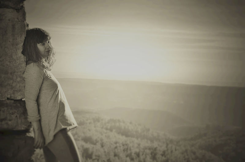 Woman leaning on wall against landscape during sunset