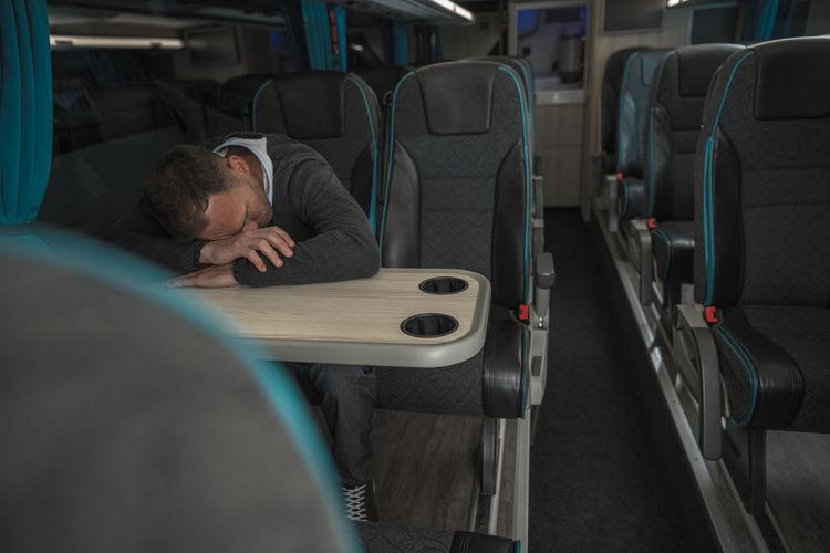 Businessman sleeping in bus