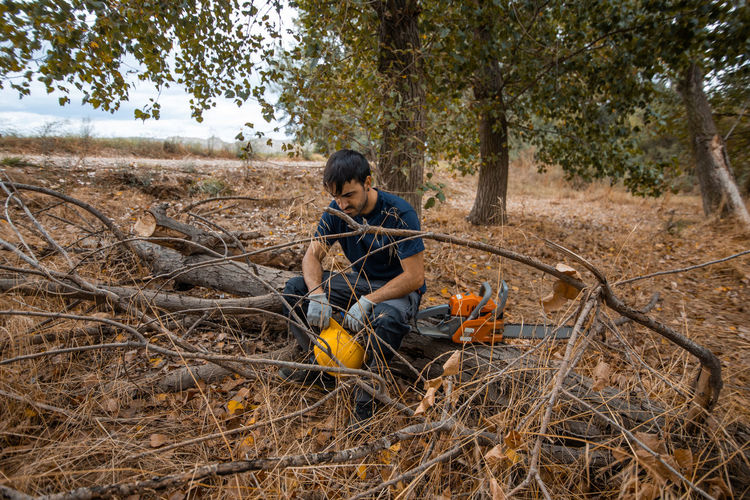 Man sitting on tree trunk with chainsaw in forest