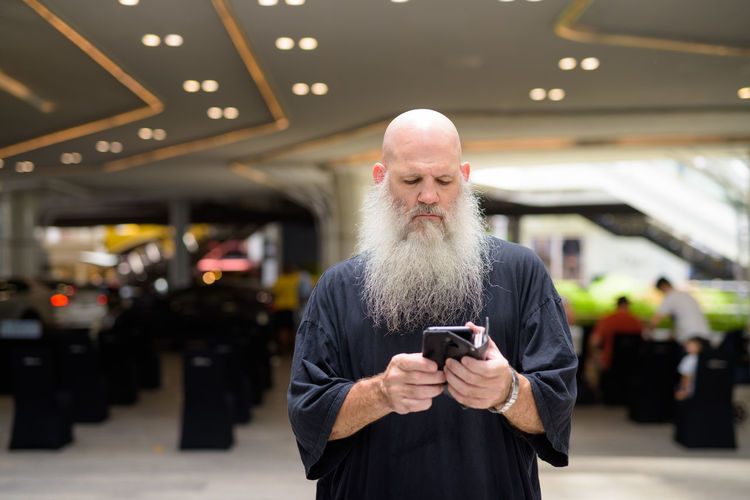 Man using mobile phone while standing on laptop