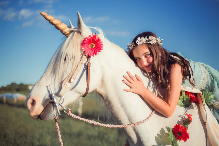 Girl with flower hair wreath sitting and leaning on white horse unicorn. Dreams come true Dreams Field Golden Horn Happiness Hugging Looking At Camera Nature Sitting Unicorn Woman Childhood Creature Fall Flower Girl Golden Hour Horse Leaning Lifestyles Magic Summer Sunset Tenderness White Wish