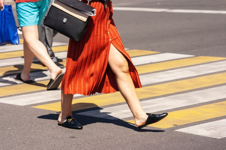 Low section of woman in high heels on road