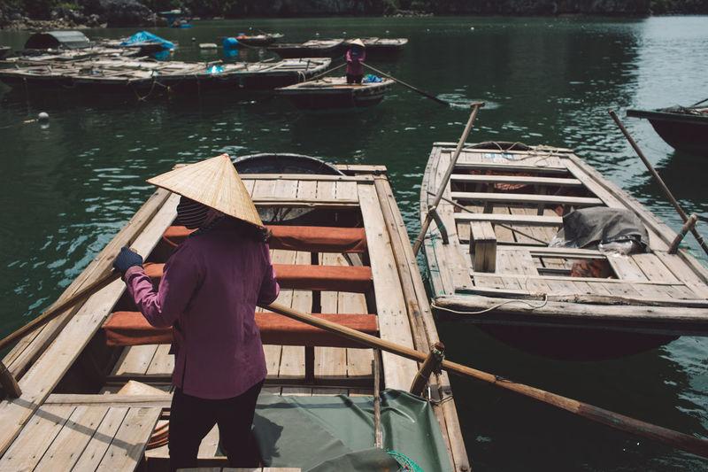 Rear view of man rowing boat in sea