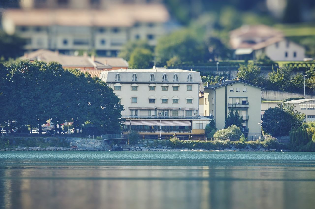 building exterior, architecture, built structure, water, building, waterfront, tree, plant, city, nature, day, reflection, no people, river, outdoors, residential district, swimming pool, pool