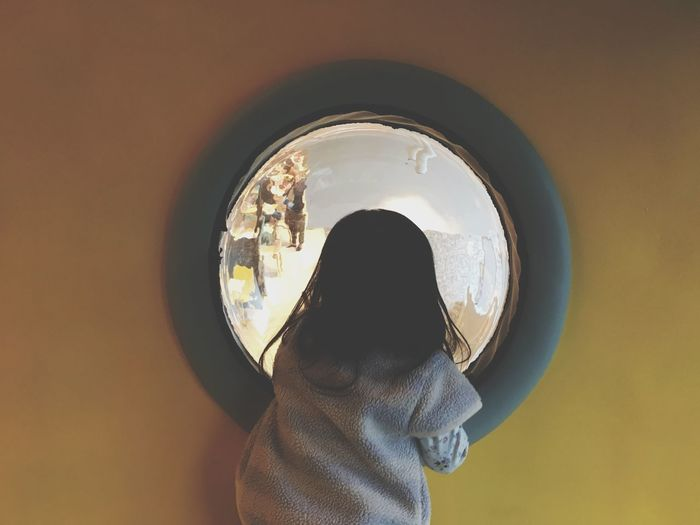 Rear view of girl looking through glass window