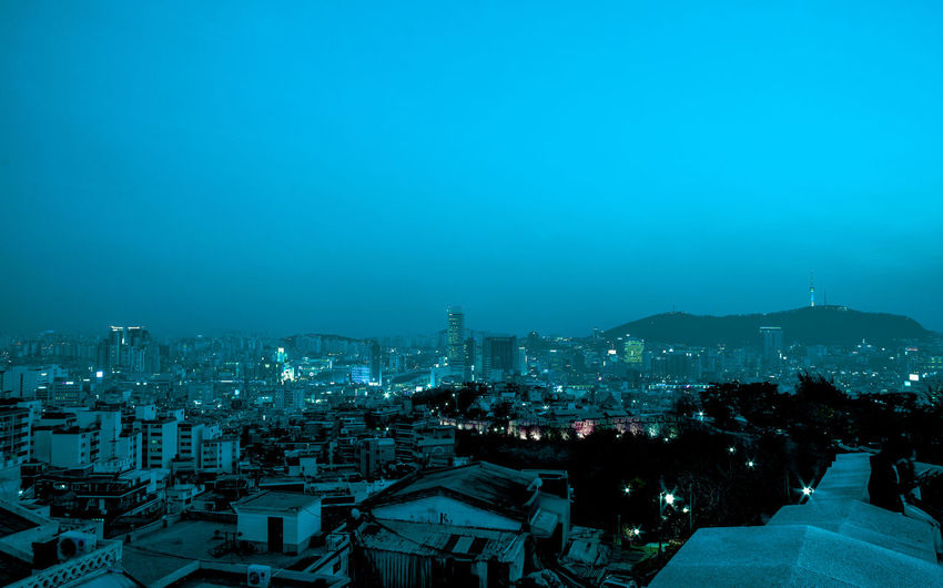 High angle view of illuminated cityscape against clear sky