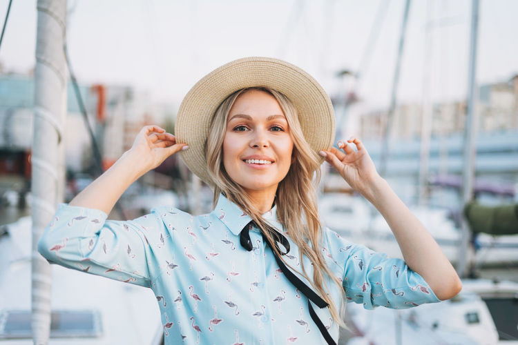 Beautiful smiling blonde young woman in blue dress and straw hat at pier in sunset time