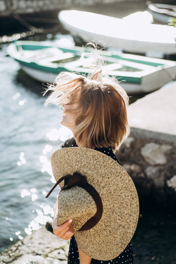 Wind in the hair of a girl sitting by the sea